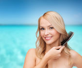 Smiling woman with hair brush — Stock Photo