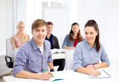 Smiling students with notebooks at school — Stock Photo