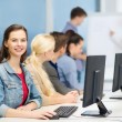 Smiling teenage girl with classmates and teacher — Stock Photo