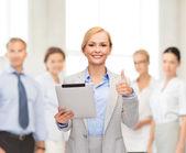 Mujer sonriente con tablet pc mostrando los pulgares para arriba — Foto de Stock