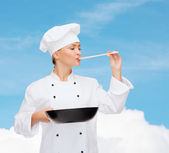 Smiling female chef with pan and spoon — Stock Photo