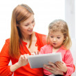 Happy mother and daughter with tablet pc computer — Stock Photo #40561823