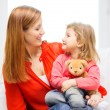 Happy mother and child with teddy bear at home — Stock Photo