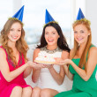 Three women wearing hats holding cake with candles — Stock Photo #40562357
