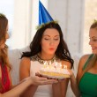 Three women wearing hats holding cake with candles — Stockfoto