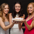 Three women holding cake with candles — Φωτογραφία Αρχείου