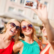 Girls taking picture with camera in the city — Stock Photo