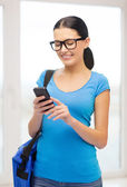 Smiling female student with smartphone and bag — Stock Photo