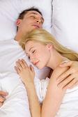Happy couple sleeping in bed — Stockfoto