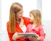 Happy mother and daughter with tablet pc computer — Stock Photo