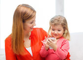 Happy mother and daughter with smartphone at home — Stock Photo