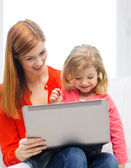 Happy mother and daughter with laptop computer — Stock Photo