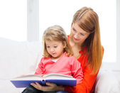 Happy mother and daughter with book — Stockfoto