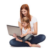 Happy mother with adorable little girl and laptop — Stock Photo