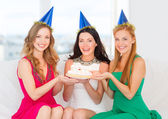 Three women wearing hats holding cake with candles — Стоковое фото