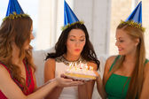 Three women wearing hats holding cake with candles — 图库照片