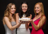 Three women holding cake with candles — Стоковое фото