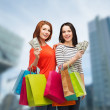 Smiling teenage girls with shopping bags and money — Foto de Stock