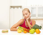 Doubting woman with fruits and hamburger — Foto Stock