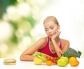 Doubting woman with fruits and hamburger — Stock Photo