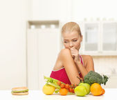 Doubting woman with fruits and hamburger — Stockfoto