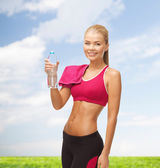 Smiling woman with bottle of water and towel — Stock Photo