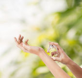 Woman hands spraying perfume — Stock Photo