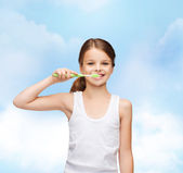 Girl in blank white shirt brushing her teeth — Stock Photo