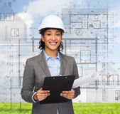 Businesswoman in white helmet with clipboard — Stock Photo
