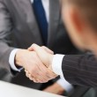 Two businessmen shaking hands in office — Stock Photo #40721481