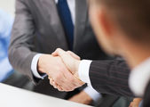 Two businessmen shaking hands in office — Stock Photo