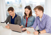 Three smiling students with laptop and tablet pc — Stock Photo