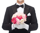Man in tail-coat with flower bouquet — Stock Photo