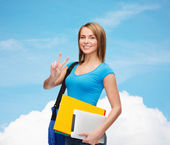 Female student with bag, tablet pc and folders — Stock Photo