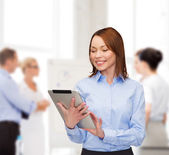 Smiling woman looking at tablet pc at office — 图库照片