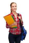 Smiling female student with bag and folders — Stock Photo