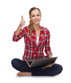 Young girl sitting on the floor with laptop — Stock Photo