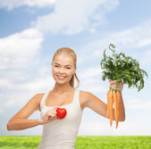 Smiling woman holding heart symbol and carrots — Stockfoto