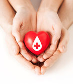 Hands holding red heart with donor sign — Stock Photo