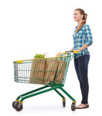 Smiling young woman with shopping cart and food — Stockfoto