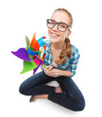 Woman in eyeglasses sitting on floor with windmill — Stock Photo