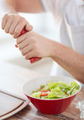 Close up of male hands flavouring salad in a bowl — Stock Photo