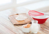 Jugful of milk, eggs in a bowl and flour — Stock Photo