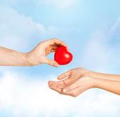 Muž rukou červené srdce s ženou — Stock fotografie