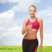 Smiling woman with bottle of water — Stockfoto