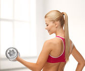 Smiling woman with heavy steel dumbbell — ストック写真