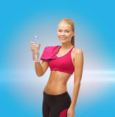 Smiling woman with bottle of water and towel — Stockfoto