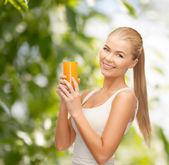 Smiling woman holding glass of orange juice — Stok fotoğraf