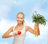 Smiling woman holding heart symbol and carrots — Photo