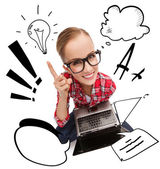 Smiling teenage girl in eyeglasses with laptop — Stock Photo